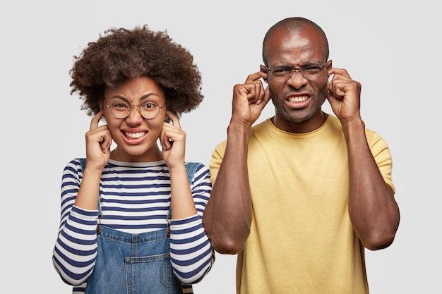 Uomo e donna dalla pelle scura disperati tappano le orecchie e stringono i denti con irritazione Foto Gratuite