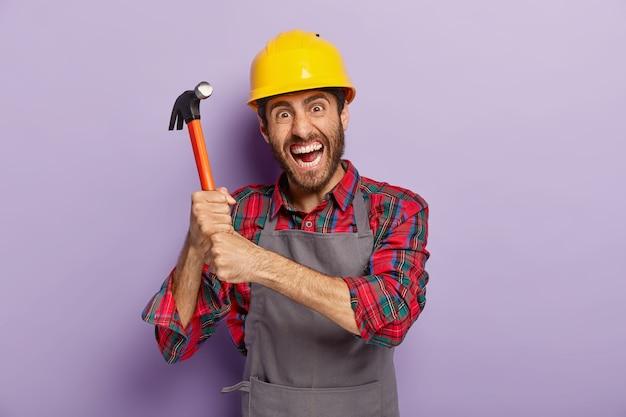절망적 인 남성 노동자 또는 수리공은 양손으로 망치를 들고, 분노한 표정, 수리 또는 조립 준비, 보호 헬멧 착용, 건설 현장에서 일하고, 실내에 서 있습니다. 무료 사진