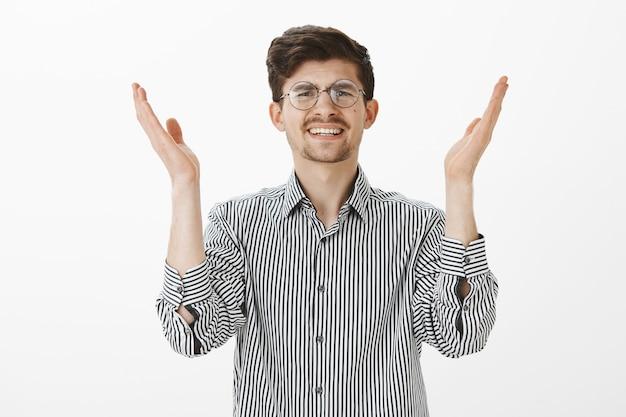 Отчаянный угрюмый европеоидный коллега в полосатой рубашке, высоко поднимающий ладонь и гримасничающий от болезненного чувства или неудовольствия, пресыщенный грудой работы или нелепыми спорами на серой стене Бесплатные Фотографии