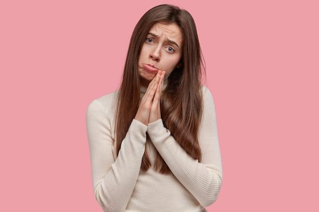 長い髪の絶望的な悲しみに満ちた若い魅力的な女性は、手のひらを祈りのジェスチャーで保ち、神に夢を実現するように頼み、恩恵を懇願します 無料写真
