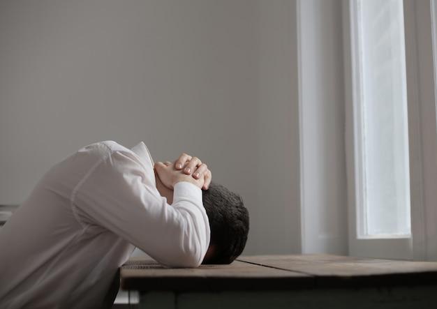 Desperate unhappy sad man at a desk Premium Photo