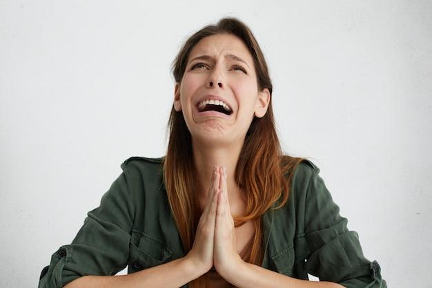 慈悲を懇願し、泣いて絶望的な女性。何かを懇願しながら悲しそうに見えるように彼女の手のひらを一緒に保持している感情的な女性。許しを求める失望した女性の泣き声 無料写真