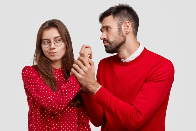 Desperate young caucasian man holds hand of girlfriend, looks with miserable expression, asks for forgiveness, feels guilty. couple have disagreement Free Photo