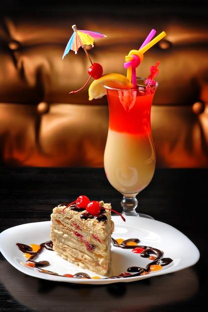 カクテルテーブルの上のチェリーで飾られた皿の上のデザートケーキ Premium写真
