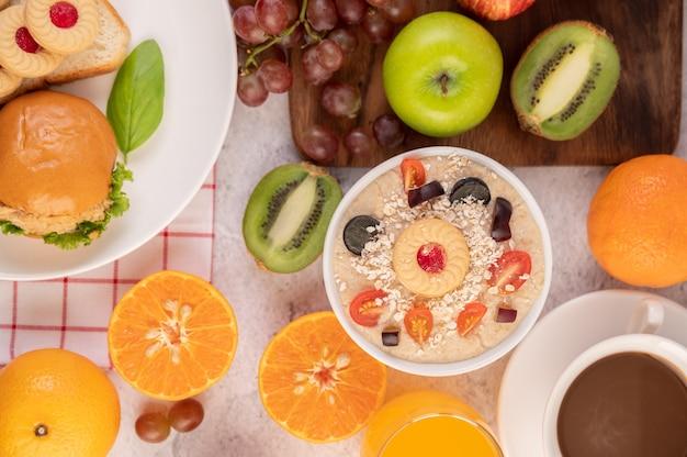 リンゴ、キウイ、オレンジ、ブドウのデザートカップ。 無料写真