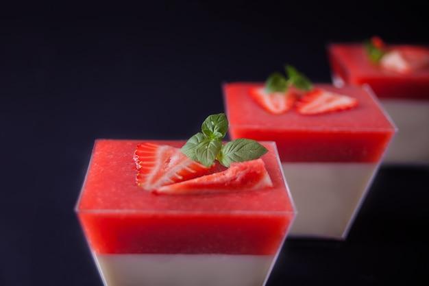 Dessert panna cotta with fresh strawberries on black Premium Photo