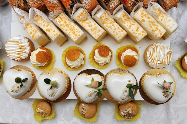 お菓子のデザートテーブル。結婚式の甘いテーブル。ゲスト用スイーツ。 Premium写真