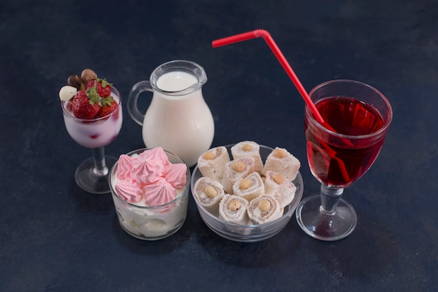 Varietà di dessert con un bicchiere di vino rosso, vista angolare Foto Gratuite