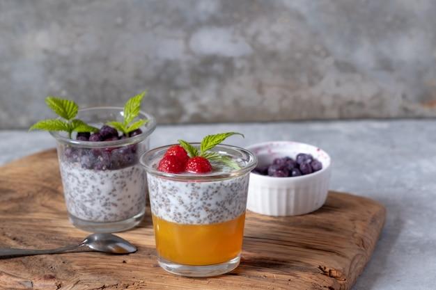 Десерт с семенами чиа и ягодами в стеклянных очках на деревянной доске на сером фоне. суперпродукты и концепция здорового образа жизни. Premium Фотографии