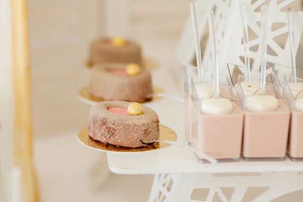 Desserts with fruits, mousse, biscuits. different types of sweet pastries, small colorful sweet cakes, macaron, and other desserts in the sweet buffet. candy bar for birthday. Premium Photo