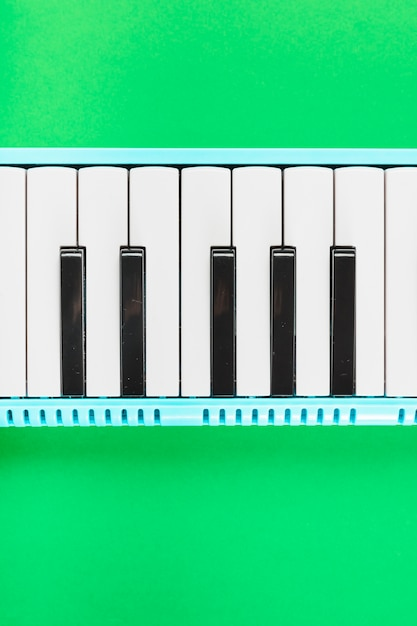 Detail of classical piano black and white keyboard on green background Free Photo