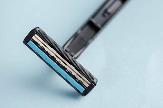 Detail of disposable black razor against blue backdrop Free Photo