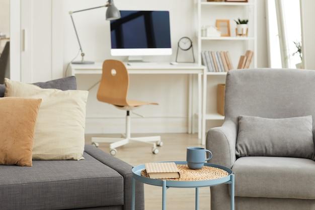 Детальное изображение интерьера уютной квартиры в современном доме с акцентом на серую мебель для гостиной на переднем плане Premium Фотографии