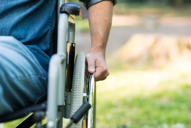 Detail of a man using a wheelchair in a park. copy-space on the right side Premium Photo