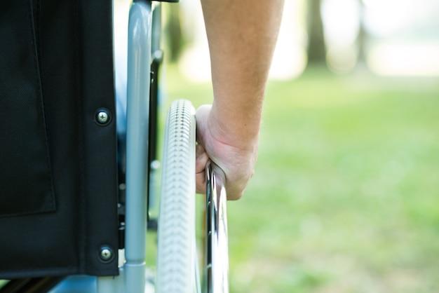 Detail of a man using a wheelchair in a park Premium Photo
