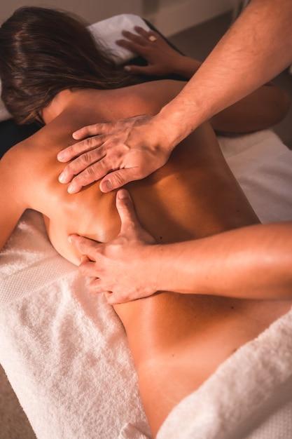 テーブルの上に横たわっている若い女性の理学療法士の背中のマッサージの詳細。理学療法、整骨、リラックスマッサージ、背中の治療のモーションビデオ Premium写真