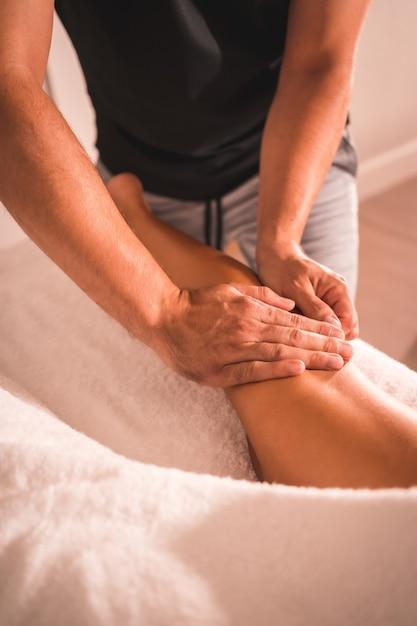 テーブルの上に横たわっている若い女性の左脚の後ろにある理学療法士のマッサージの詳細。理学療法、整骨、リラックスマッサージ、背中の治療のモーションビデオ Premium写真