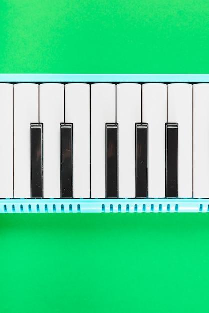 Деталь классической черно-белой клавиатуры пианино на зеленом фоне Бесплатные Фотографии