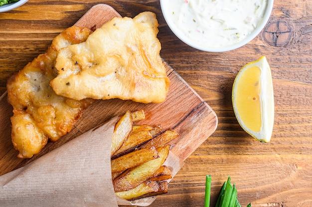 Деталь рыбных чипсов с дипом и лимоном, пюре из мятного горошка, соус тартар в бумажном рожке Premium Фотографии