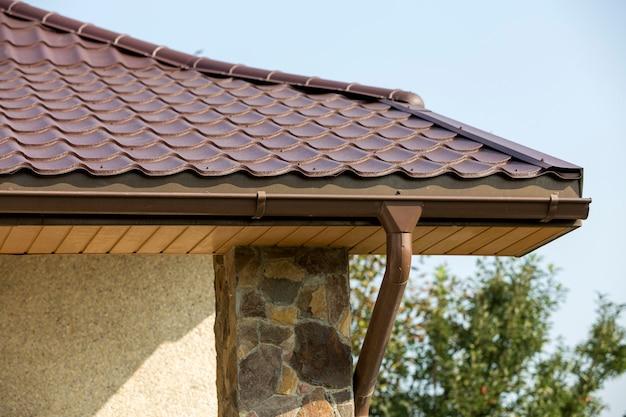 Деталь нового современного дома угол дома с штукатуркой стен, украшенных натуральными камнями, коричневой черепичной крышей и водосточной трубы на голубом небе. недвижимость . Premium Фотографии