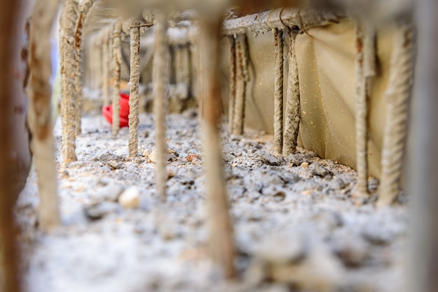 Деталь стальных стержней внутри цемента для железобетона фундамента стены строящегося здания Premium Фотографии