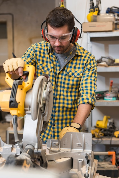 Detail of professional male worker using a mitre-saw in the workshop Free Photo