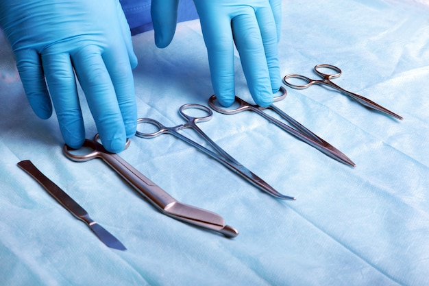 Detail shot of sterilized surgery instruments with a hand grabbing a tool Premium Photo