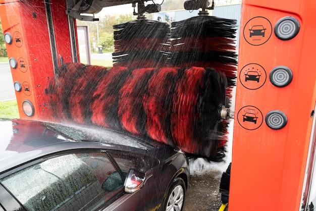 Детальный вид на автомойку, пенную воду для автомойки, автоматическую автомойку в действии Premium Фотографии