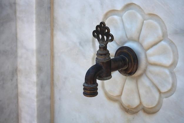 Detail of a water tap valve twist marble walls. Premium Photo