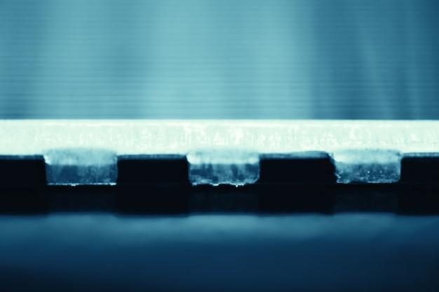 Детальная предпосылка части автомобильного радиатора в макросе с космосом экземпляра. монохромное изображение металлического автозапчасти крупным планом. пустая поверхность стальной текстуры в голубом тоне. Premium Фотографии