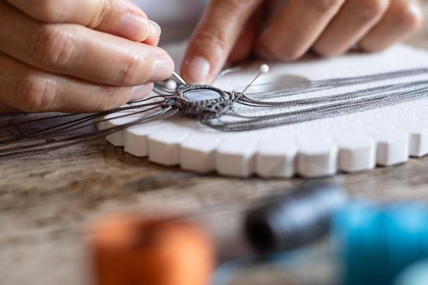 Детальный макро-крупный план женских пальцев, работающих над завязанным вручную браслетом из микромакраме с размытыми катушками ниток в эффекте боке Premium Фотографии