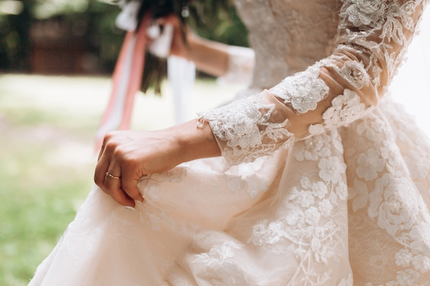 Details Of Bridal Wedding Dress Hand With Wedding Ring Outdoors