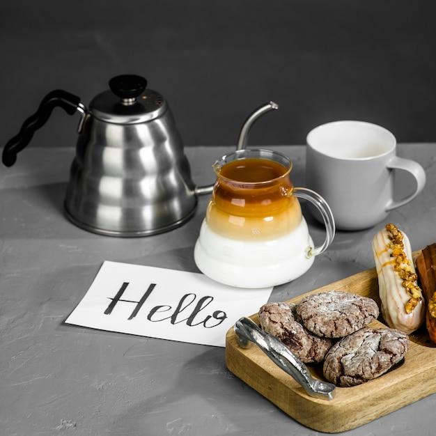 灰色のテーブルでの朝食の詳細。コーヒー、長い注ぎ口のあるティーポット、お菓子、そしてこんにちはの碑文が書かれたカード。フィルタードリッパーでコーヒーを淹れる。コーヒーを作る別の方法。 Premium写真