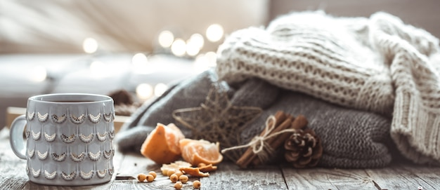 Details of still life in the home interior living room. beautiful cup of tea with tangerines and sweaters on wooden background . cosy autumn-winter concept Free Photo