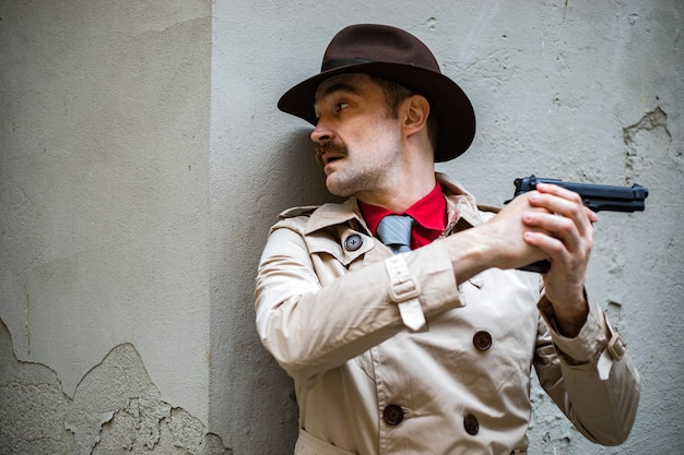 Detective taking cover and aiming with his handgun Premium Photo