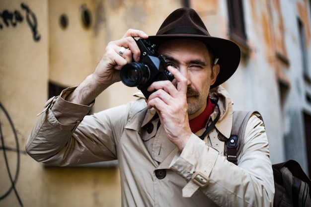 Detective taking pics in a sity slum with his vintage camera Premium Photo