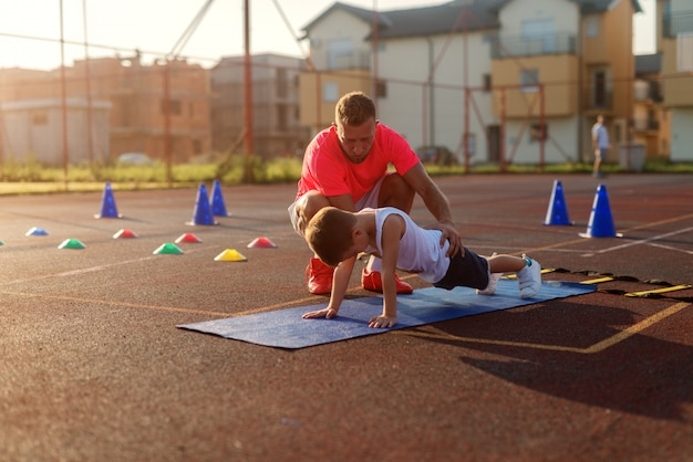 Determinative young football coach learning little boy how to do push ups. Premium Photo