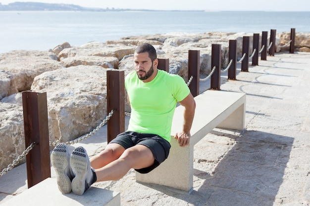 Determined Sporty Man Doing Triceps Dips on Benches Free Photo
