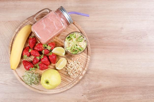 デトックスは、ドリンク、フルーツ、ベリーのスムージーの成分を浄化します。減量ダイエットや空腹時の自然で有機的な健康ジュース。イチゴ、マイクログリーン、バナナの栄養ドリンクのメイソンジャー Premium写真