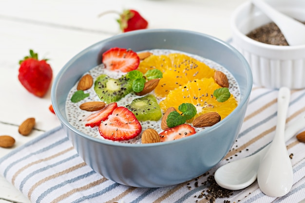 Detox and healthy superfoods breakfast in bowl. vegan almond milk chia seeds pudding with strawberries, orange and  kiwi. Free Photo