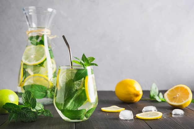 Detox water or lemonade with lemon mint, citrics in glass on wooden table and grey backdrop. Premium Photo