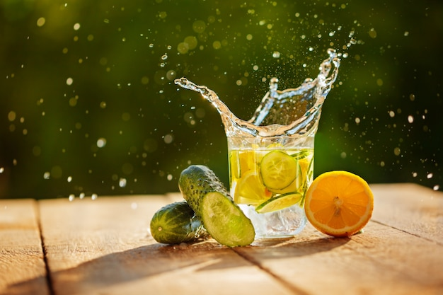 Detox water with lemon and cucumbers with splash on wooden table and green nature background Premium Photo