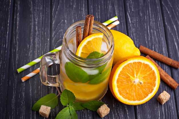 Detox water with orange, mint and cinnamon in jar Premium Photo