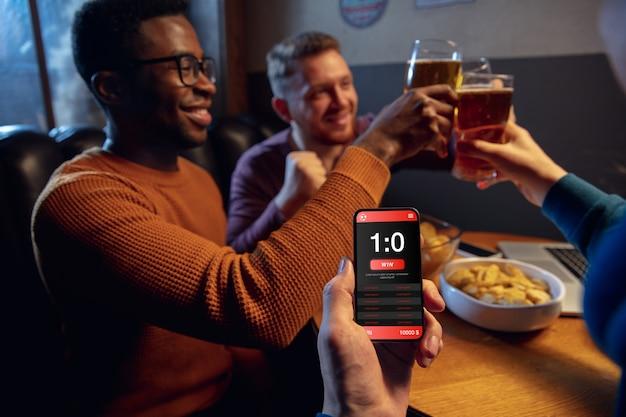 Schermo del dispositivo con app mobile per scommesse e punteggio. dispositivo con i risultati della partita sullo schermo, fan entusiasti sullo sfondo durante la partita. Foto Gratuite