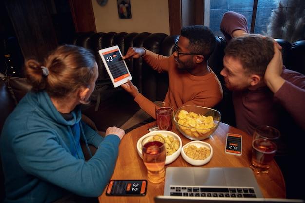 賭けとスコアのためのモバイルアプリを備えたデバイス画面。画面に試合結果が表示され、試合中にバックグラウンドでファンが興奮しているデバイス。 無料写真
