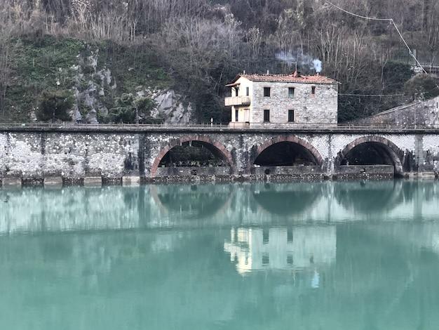 緑に覆われた丘とイタリアの水に映る家々に囲まれた悪魔の橋 無料写真