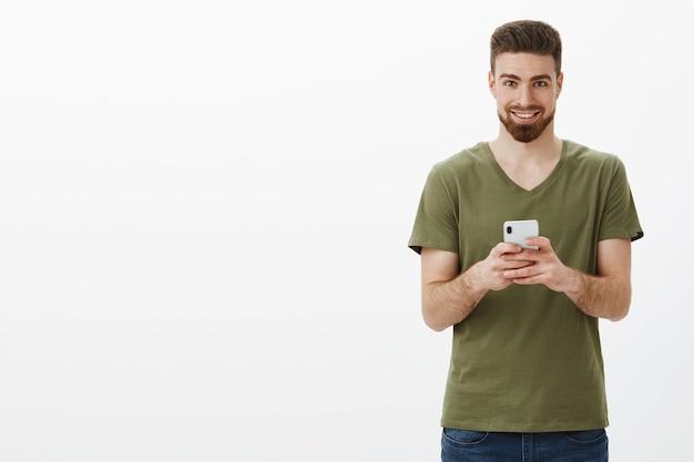 Uomo barbuto maturo di bell'aspetto subdolo ed eccitato in maglietta verde oliva che tiene smartphone e che sembra felice sorridendo come se avesse un'idea interessante del prossimo post online sul muro bianco Foto Gratuite