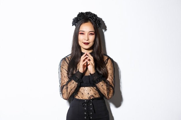 고딕 레이스 드레스에 사악한 젊은 아시아 여자 기쁘게 웃 고 손가락을 첨탑. 마녀는 사악한 계획을 준비하고 교활한 미소를 지으며 카메라를 봅니다. 할로윈 개념. 무료 사진