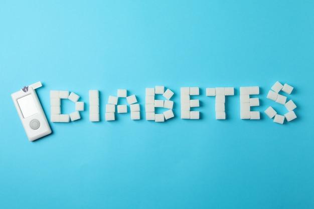 砂糖の立方体と青の背景に血糖計で作られた糖尿病 Premium写真