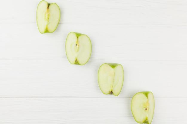 Diagonal of apples slices on white background Free Photo